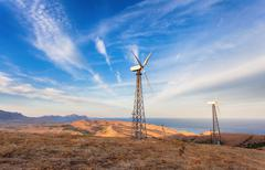 Industrial landscape with wind turbine generating electricity in mountains Stock Photos