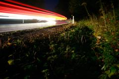 Roadside with light streaks from cars Stock Photos