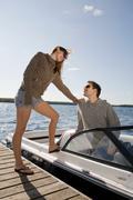 Couple with speedboat next to dock - stock photo