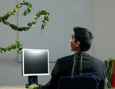Man by desk beeing attacked by plants Stock Photos