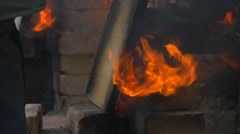 Brick Furnace For Clay and Enamel Burning Man Puts the Piece of Wood Into Fire Stock Footage