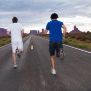 Two men jogging on road in desert Kuvituskuvat