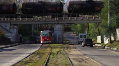 Tram passes under the bridge on which there is a freight train. Stock Footage