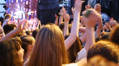Crowd people fan spectators raise swaying hands in air enjoy music concert Stock Footage