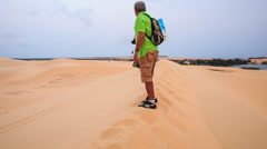 Old Man Arranges Selfie Stick on Crest in White Sand Dunes Stock Footage