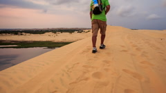 Tourist Walks along Crest in White Sand Dunes against Skyline Stock Footage