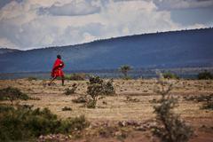 Man walking across dry terrain Stock Photos