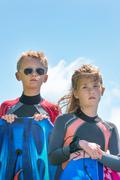 Children in wetsuits with surfboards - stock photo