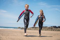 Children in wetsuits carrying surfboards - stock photo