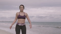 Young woman working out on the beach at cloudy weather. Stretching. Fitness - stock footage