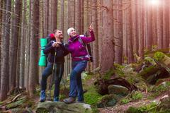Man and Woman Hikers Staying in Dense Old Forest Smiling and Pointing Stock Photos