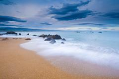 Waves washing up on sandy beach Stock Photos