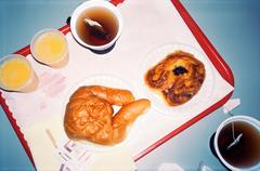 Baked pastries, tea and juice on tray Stock Photos