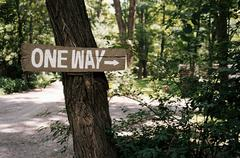 'One way' sign on tree in forest Stock Photos