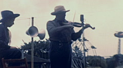 USA 1940's: man playing violin at a fair - stock footage