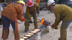 Three Workers Pouring Molten Metal Into Molds Carefully and Quickly Festival of Stock Footage