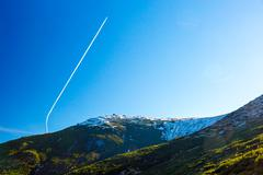 Morning Mountain View and Airplane Vapor Trail on Deep Blue Sky - stock photo