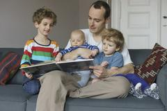 Happy family reading book while sitting on sofa at home Stock Photos