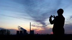 A young girl takes pictures of a power plant at the evening Stock Footage