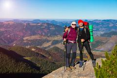 Two Hikers Staying on High Rock and Mountain View with Autumnal Forest Stock Photos