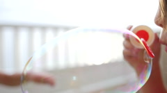 Girl blows big soap bubble Stock Footage