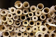 Rolls of fabric in textiles factory - stock photo