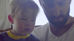 Child points out thing on cell phone to dad Stock Footage