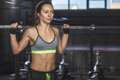 Young determined athlete lifting barbell at health club Stock Photos