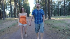 A man & woman taking a leisurely stroll in the woods - stock footage