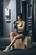 Young female boxer wrapping hand wrap while sitting at gym - stock photo