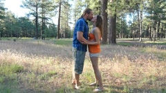 A young man kisses and picks up his girl Stock Footage