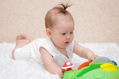 Little baby girl playing with a toy Stock Photos