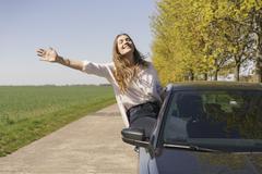 Cheerful woman sitting on car window at roadside Stock Photos