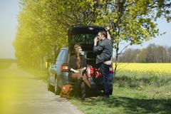 Woman sitting in car trunk besides man on roadside during sunny day Stock Photos