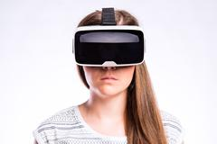 Woman with virtual reality goggles. Studio shot, gray background - stock photo