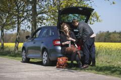 Woman sitting in car trunk besides man on roadside Stock Photos