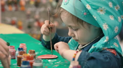 Little, cute girl paints the wooden figure - stock footage