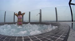 Smiling girl in sunglasses in bikini standing in Jacuzzi on the sky hotel roof Stock Footage