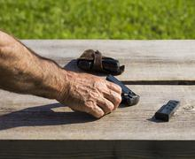 Hand touching a gun - stock photo