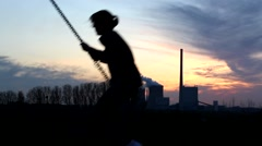 A young girl is swinging with a nice sunset and Power Plant Stock Footage