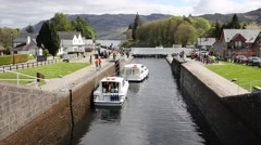 Boats moving through lock gates Caledonian Canal Fort Augustus Scotland uk Stock Footage