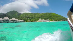 SLOW MOTION: Boat ride past luxury overwater villas in sunny exotic island - stock footage
