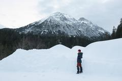 Woman standing on snow covered field against mountains Kuvituskuvat