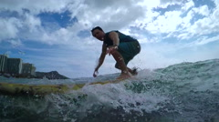 SLOW MOTION: Young man learning to surf at famous surf spot in Waikiki beach Stock Footage