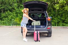 Vacation, Travel - young woman ready for the traveling. suitcases and car Kuvituskuvat