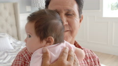 Grandfather Holding Baby Granddaughter In Slow Motion Stock Footage
