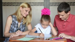 Schoolgirl doing homework with their parents smile looked into the frame - stock footage