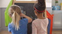 Two Girls Drawing Picture On Blackboard Shot On R3D Stock Footage