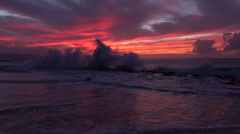 SLOW MOTION: Dramatic view of big wave crashing into coral reef under pink skies - stock footage