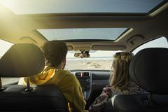 Rear view of couple in car at beach on sunny day - stock photo